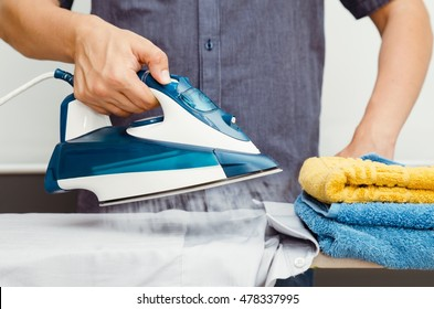 Man irons clothes on ironing board with blue steaming iron