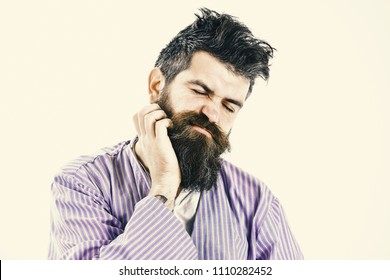 Man with itchy face wake up, scratching beard with hand. Man tired, still need rest, white background. Hipster with beard, mustache and messy hair itching, copy space. Hangover morning concept.
