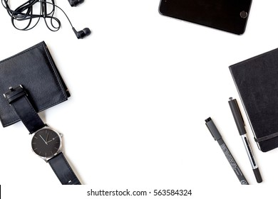 Man Items in all Black on a White Background Shot from Above with Cell Phone, Pens, Wallet, Watch, Notebook, and Headphones