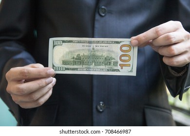 A man in a jacket holds a hundred-dollar bill in front of him with both hands. Close-up, you can see the whole bill
