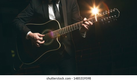 Man in jacket plays and sings while standing on stage on a 12-string acoustic guitar. Dark background and blurred back light