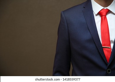 a man in a jacket and red tie on a dark background close up with copy space. shoulder of a businessman in a red tie on a dark background
