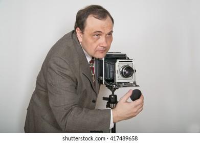 Man in jacket and tie aiming retro photo camera