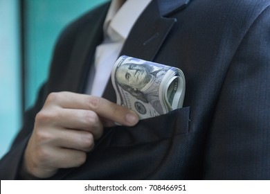 A man in a jacket or a tuxedo puts a bundle of hundred-dollar bills in his breast pocket, close up