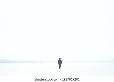 a man in a jacket walks through a blizzard on a frozen lake. small person in a large clean space. White sky . place for the test on a white background. matrimony in nature. everything is white.