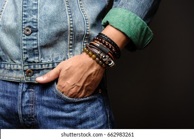 The man in jean jacket wearing bracelets, casual style of men accessories. Shallow depth of field.