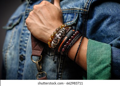 The man in jean jacket wearing bracelets, casual style of men accessories. Shallow depth of field.