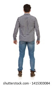 Man in jeans, boots and lumberjack shirt is standing relaxed. Rear view. Full length studio shot isolated on white.