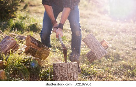 Man in jeans and checkered shirt chopping wood with axe