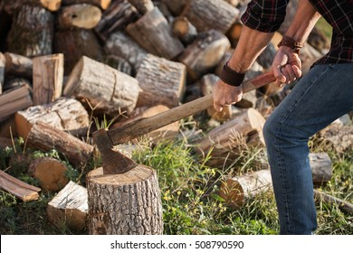 Man in jeans and checkered shirt standing near stump with ax in hands