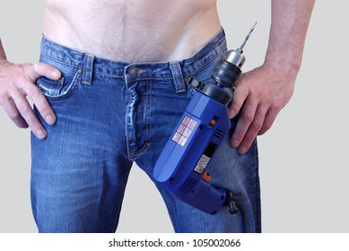 A man in jeans with a drill