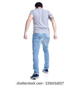 Man in jeans goes clenching fists angry on white background isolation, back view