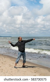 A man in jeans and gray trowel is on the beach in the sand and throws into the sea .