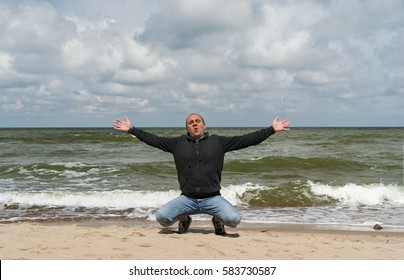 A man in jeans and gray trowel set down on the sea shore on the sand and spread his arms out to the sides.
