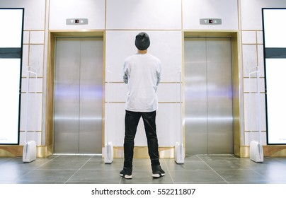 Man in jeans and hat standing between the elevators with crossed arms on his chest. Young guy is waiting for a lift. View from the back