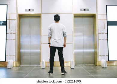 Man in jeans and hat standing near the two elevators with hands down. He is waiting for somebody downstairs. View from the back