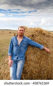 Man in jeans in   hay on  field.