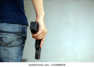 Man in a jeans holding a gun on white wall. Robbery attack concept,copy space.