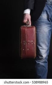 Man in jeans, holding an old brown suitcase on a black background