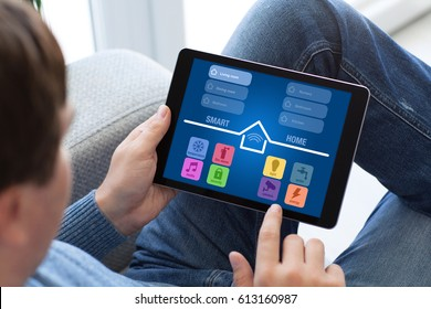 man in jeans holding tablet with app smart home on screen
