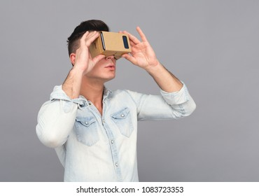 Man in jeans shirt using carboard vr headset and looking aside.