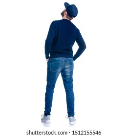 Man in jeans shorts, cap, casual clothing standing looking up on white background isolation, rear view