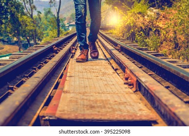 Man jeans and sneaker shoes walking on Railroad