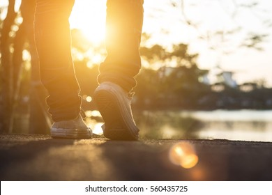 Man jeans and sneaker shoes walking on the road sunset light