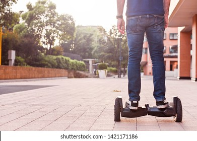 A man in jeans and sneakers on a hoverboard ride in the city. Happy boy riding around at sunset. Modern electronics for relaxation and entertainment. Sun glare on the photo. Copy space.