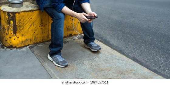 man with jeans and sneakers sitting on a yellow metal and cement blocker playing with his mobile device