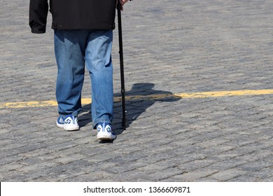 Man in jeans and sneakers walking with cane on a street, shadow on pavement. Old person on the sidewalk, concept for disability, old age, limping
