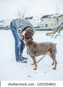 A man in jeans and a sweater bending down towards his dog to give him a warm nuzzling embrace out in the snow, in the middle of a neighborhood playground.