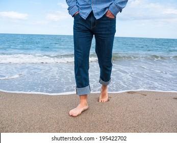 Man in jeans walking along the coast