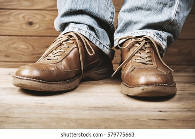 man in jeans wearing old brown leather shoes (Shallow depth of field)