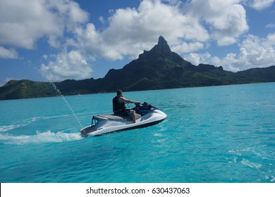 Man jet skiing in tropical water