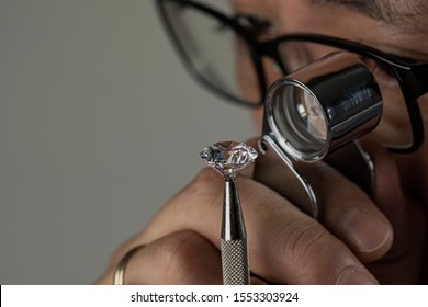 Man jeweller examines polished diamond through magnifier. Buyer checking diamond. Cut and polished diamond. Diamond jewellery under grading. Jeweller looking through loupe.