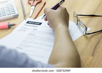 A Man Or Job Seeker Review His Resume On His Desk Or Review His Resume  Before