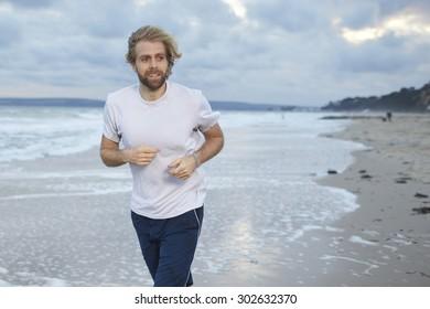 A man jogging along the beach
