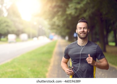 Man joggt entlang eines Baumes auf einer belebten Straße, die sich der Kamera in einem aktiven Lifestyle-Konzept nähert