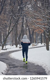 Man jogging in a cold winter snowy day outdoors.