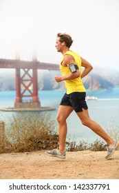 Man jogging - male running in San Francisco. Sporty fit young man jogger along a dirt track alongside San Francisco Bay and Golden Gate Bridge. Runner listening to training music from smartphone.