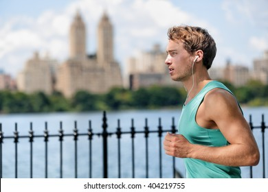 Man jogging in Manhattan Central Park during summer Male Caucasian runner running in New York City along the lake with view on skyscrapers background. New yorker living a healthy and fit lifestyle.