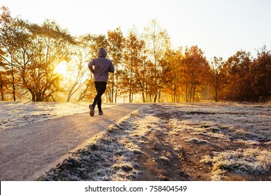 Man jogging on cold sunny winter morning in the park