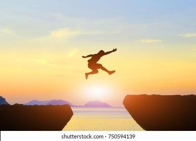 Man jump Mountain cliff sun light over silhouette