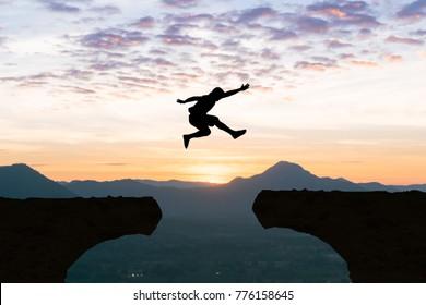 Man jump Mountain cliff sun over silhouette