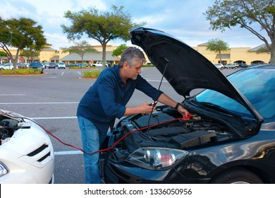 A man is jump starting a car with jumper cables helping person with a disabled automobile due to a dead battery at a shopping mall parking lot.