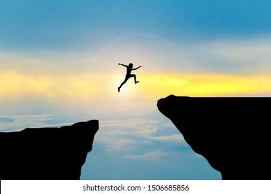 Man jump through the gap between hill.man jumping over cliff
