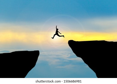 Man jump through the gap between hill.man jumping over cliff