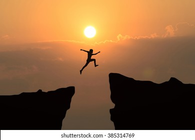 Man jump through the gap between hill.man jumping over cliff on sunset background,Business concept idea