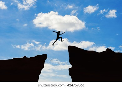 Man jump through the gap between hill.man jumping over cliff on sunset background,Business concept idea ,Olympic or sport symbol